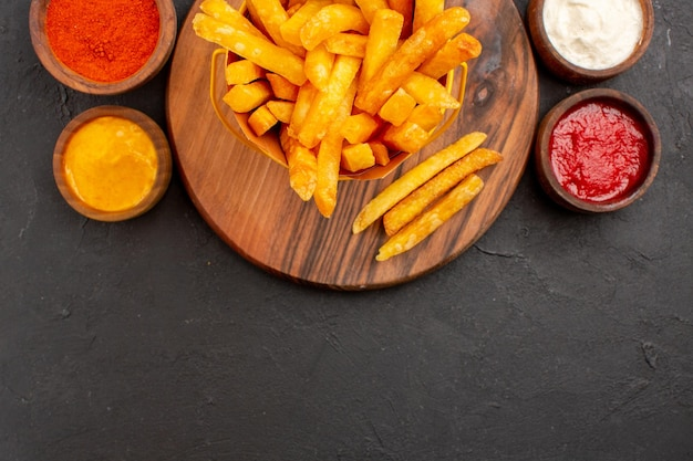 블랙에 소스와 함께 맛있는 감자 튀김의 상위 뷰