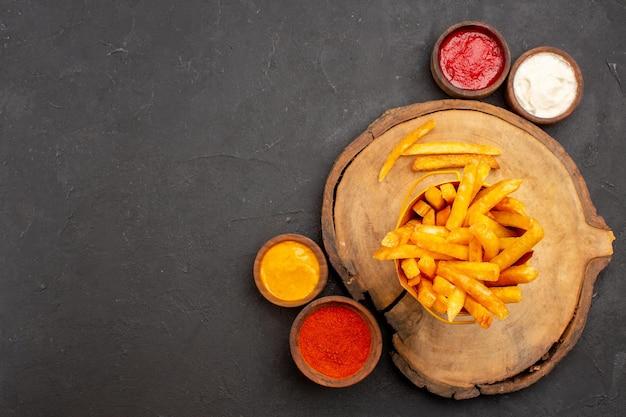 어둠에 소스와 함께 맛있는 감자 튀김의 상위 뷰