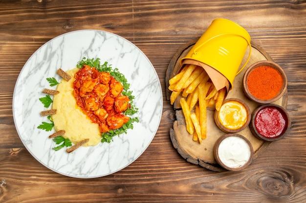갈색 테이블에 조미료와 닭고기 식사와 함께 맛있는 감자 튀김의 상위 뷰