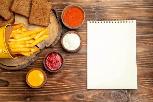 茶色のテーブルに調味料とおいしいフライドポテトの上面図