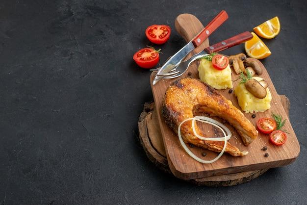 まな板カトラリーのおいしい揚げ魚とキノコのトマトグリーンの上面図黒の表面にコショウをセット