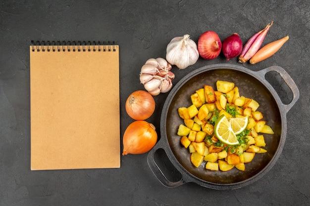 暗い表面にレモンとニンニクが周りにある鍋の中のおいしいフライドポテトの上面図