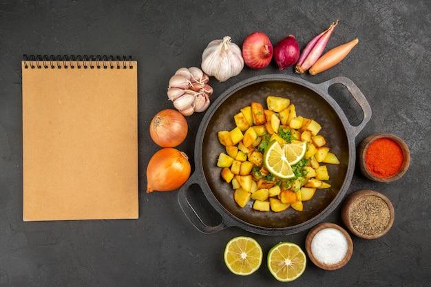 暗い表面に玉ねぎとニンニクが周りにある鍋の中のおいしいフライドポテトの上面図