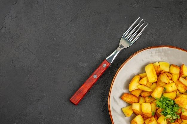 어두운 표면에 채소와 함께 접시 안에 맛있는 튀긴 감자의 상위 뷰