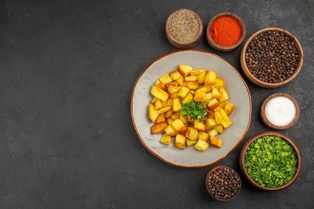 Вид сверху вкусного жареного картофеля внутри тарелки с приправами на темной поверхности