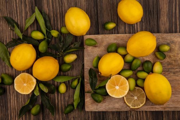 나무 표면에 나무 주방 보드에 고립 된 kinkans 및 레몬과 같은 맛있는 과일의 상위 뷰