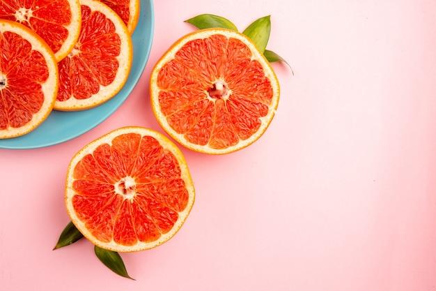 Вид сверху вкусных кусочков фруктов грейпфрутов внутри тарелки на розовой поверхности