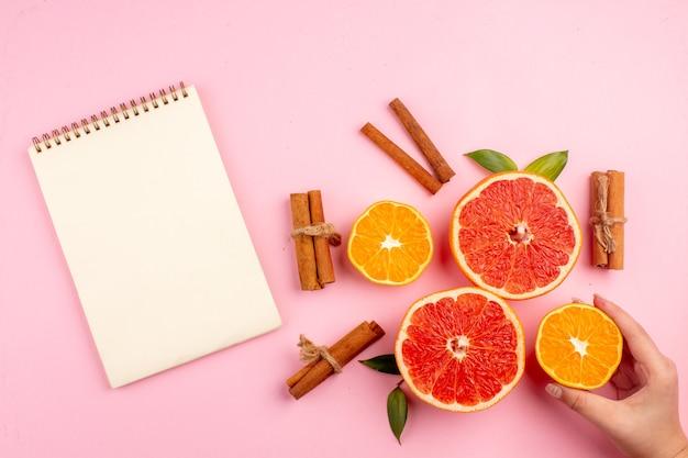 Вид сверху вкусных кусочков фруктов грейпфрутов с корицей на розовой поверхности