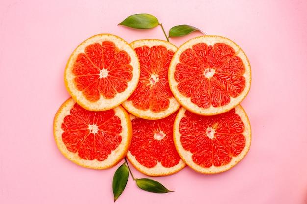 Вид сверху вкусных грейпфрутов сочных кусочков фруктов на розовой поверхности