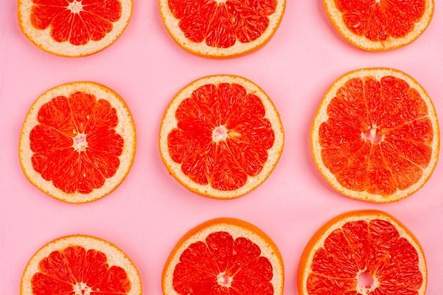 ピンクの表面に並ぶおいしいグレープフルーツの上面図