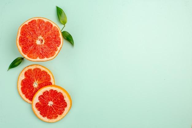 Вид сверху вкусных грейпфрутов, нарезанных сочных фруктов на голубой поверхности