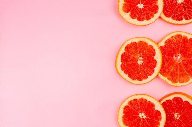 Вид сверху вкусных грейпфрутов, нарезанных сочных фруктов на светло-розовой поверхности