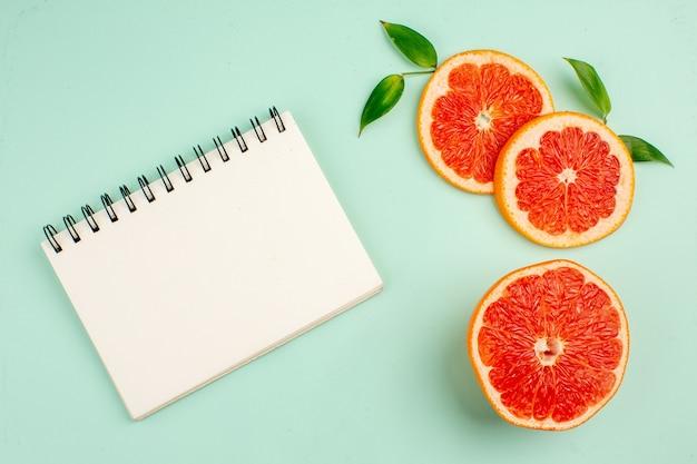 Вид сверху вкусных грейпфрутов, нарезанных сочными на голубой поверхности