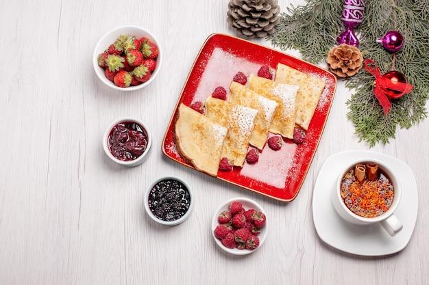白のお茶と果物のカップとおいしいパンケーキの上面図