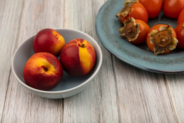 Вид сверху вкусных персиков на миске с мягкой свежей хурмой на тарелке на серой деревянной поверхности