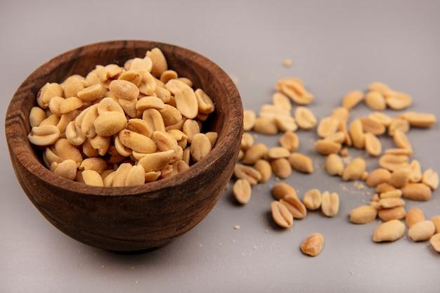 Вид сверху вкусных кедровых орехов на деревянной миске с изолированными кедровыми орехами
