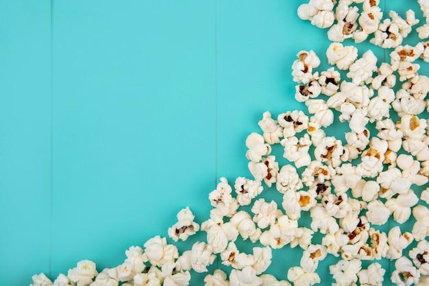 Вид сверху вкусных попкорнов, изолированных на синей поверхности