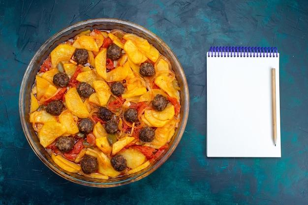 진한 파란색 표면에 미트볼과 토마토와 함께 맛있는 감자 식사의 상위 뷰