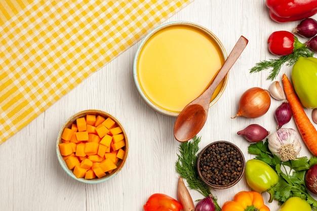 白いテーブルの上の野菜でテクスチャード加工されたおいしいカボチャスープクリームの上面図