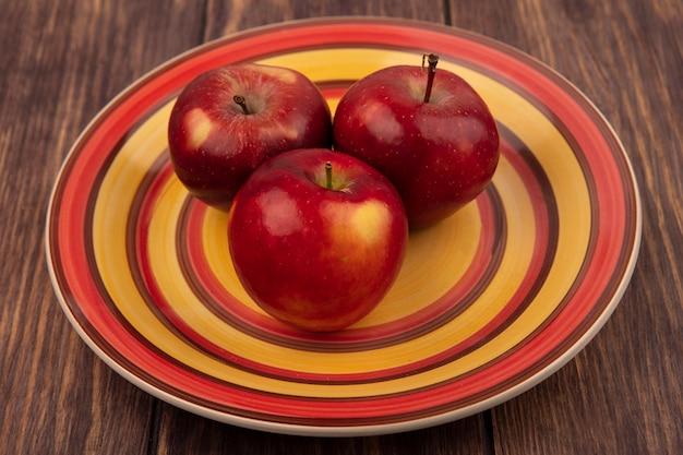 나무 표면에 접시에 맛있는 빨간 사과의 상위 뷰