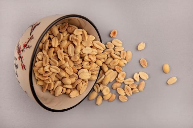 Вид сверху на вкусные жареные соленые кедровые орехи, падающие из миски