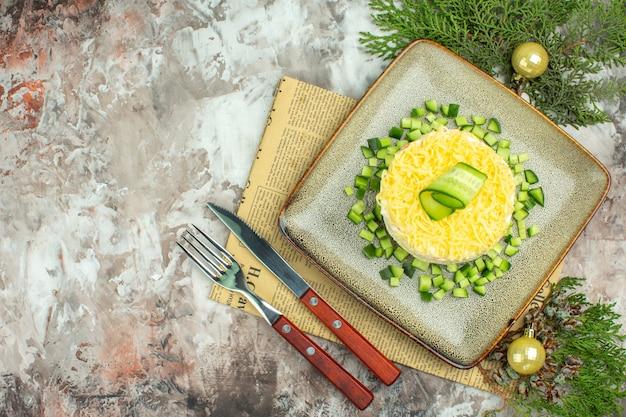混合色の背景に古い新聞の装飾アクセサリーに刻んだキュウリとナイフフォークを添えておいしいサラダの上面図