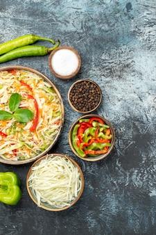 Вид сверху вкусного салата со свежими овощами на темной поверхности