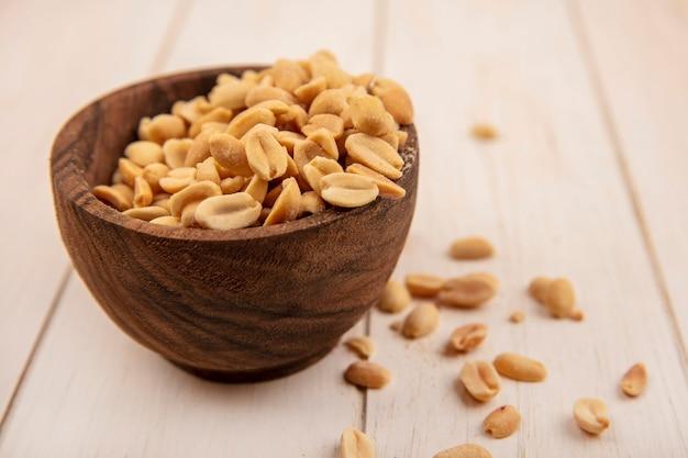 Вид сверху вкусных соленых сосновых шишек на деревянной миске на бежевом деревянном столе
