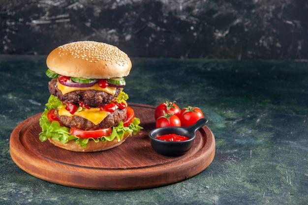 暗い色の表面の右側にある木製のまな板においしいサンドイッチトマトケチャップの上面図