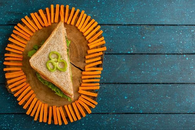 Вид сверху вкусного бутерброда с зеленым салатом, ветчиной и помидорами в качестве начинки на синей деревенской поверхности