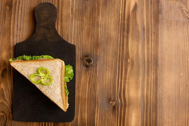 Вид сверху вкусного бутерброда с зелеными помидорами салата на коричневой деревянной поверхности