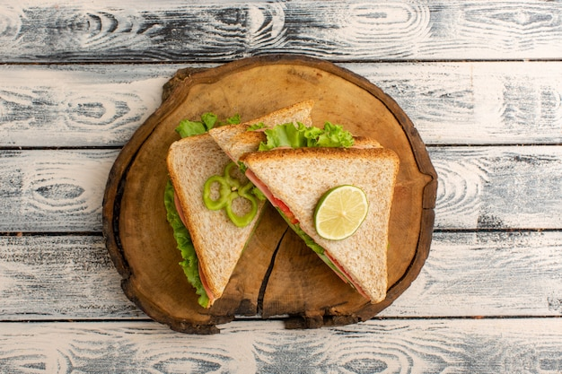 Вид сверху вкусных бутербродов на деревянном столе и серой деревенской поверхности