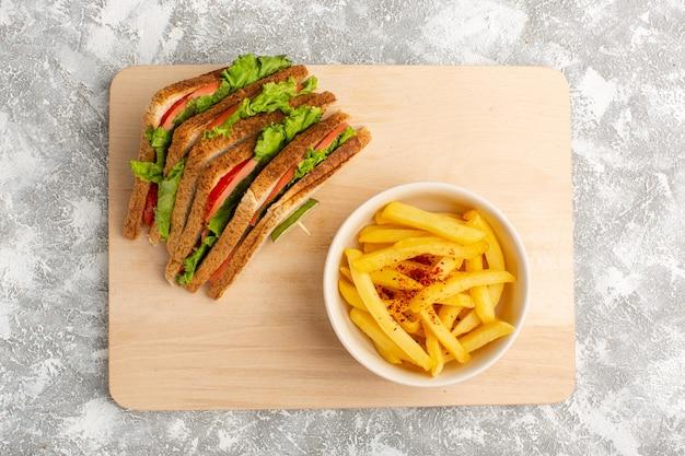 Вид сверху вкусных бутербродов с зеленым салатом, помидорами, картофелем фри на светлом столе