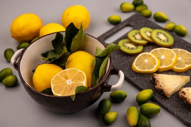 Вид сверху вкусных кусочков фруктов, таких как киви, ананас и лимон на черной кухонной доске с лимонами на миске с кинканами и лимонами, изолированными на серой стене