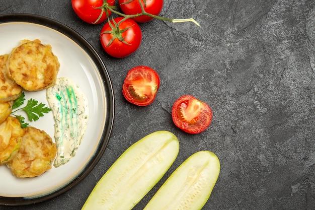 Вид сверху вкусной тыквенной еды, нарезанной вареными овощами на серой поверхности