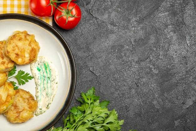 Вид сверху вкусной кабачковой муки, нарезанной вареными овощами с помидорами на серой поверхности