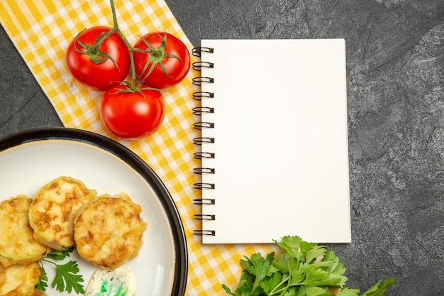 灰色の表面にトマトとおいしいスカッシュミールスライス調理野菜の上面図