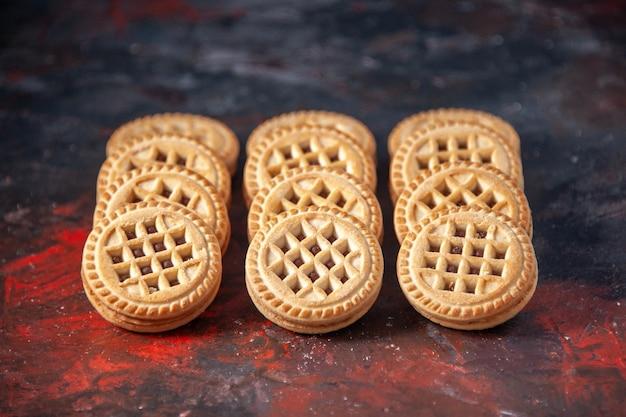 空きスペースのある混合色の背景に3列に並べて配置されたおいしいシュガークッキーの上面図