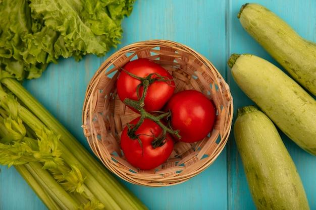 Вид сверху вкусных помидоров на ведре с салатом, цукини и сельдереем, изолированных на синей деревянной поверхности