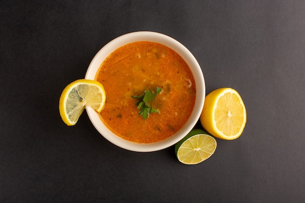 暗い表面にレモンと一緒にプレート内のおいしい野菜スープの上面図