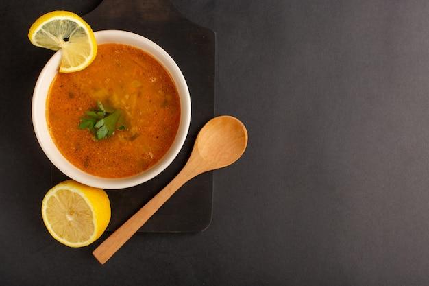 暗い表面にレモンスライスとプレート内のおいしい野菜スープの上面図