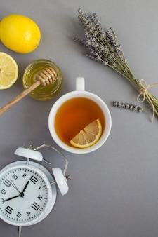 회색 배경에 찻잔, 흰색 알람 시계, 마른 라벤더, 레몬, 꿀의 꼭대기 전망. 불면증에 대한 약초.