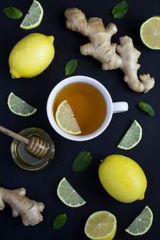 木製の背景にレモン、生姜、蜂蜜と白いカップのお茶の平面図です。スペースをコピーします。