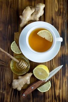 Вид сверху чая в белой чашке с лимоном, медом и имбирем на деревянных фоне. крупный план. расположение вертикальное.