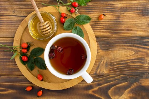 Вид сверху чая с шиповником и медом на деревянной разделочной доске