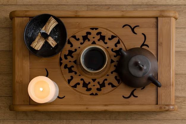 Вид сверху на чашку, чайник и горящую свечу