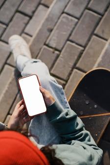 Вид сверху подростка на открытом воздухе с помощью смартфона