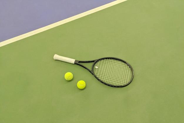 녹색 점토 테니스 코트에서 테니스 라켓과 두 공의 상위 뷰.