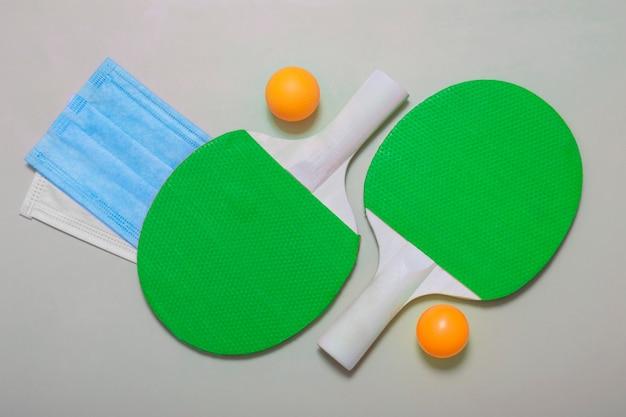 Вид сверху теннисных ракеток, мяча и медицинских масок на бежевом фоне. развлечение на свежем воздухе во время карантина, пандемии.