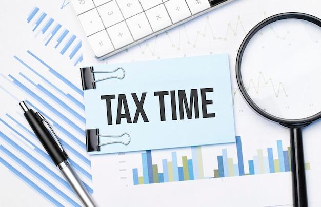 금융 차트에 계산기, 돋보기 및 펜이있는 텍스트 세금 시간의 상위 뷰